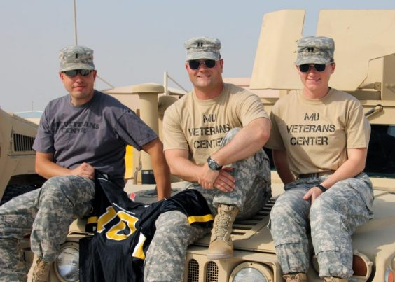 Three people sitting on a military vehicle wearing MU Veterans Center shirts