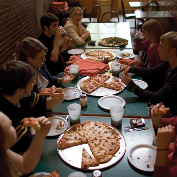 Group eating pizza at tables