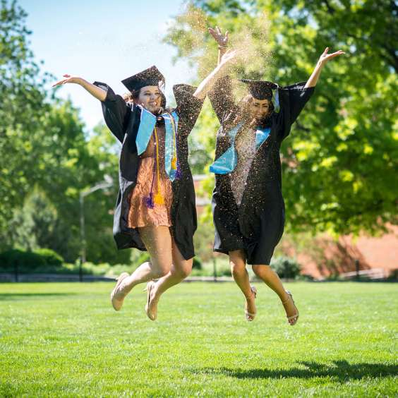 Two graduates in caps and gowns jumping with glitter