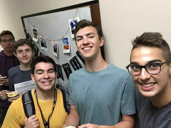 Mizzou student Joshua Reneau stands in the hallway of a residence hall with a group of fellow freshmen, all smiling at the camera