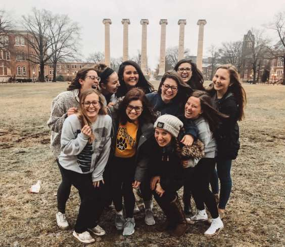 Ten members of the Mizzou tour team pose in front of the Columns with their arms around each other